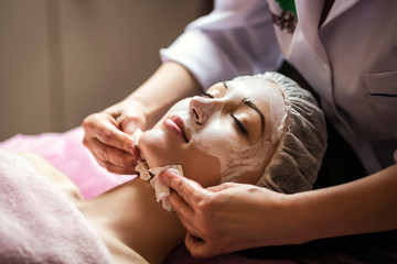 woman getting facial care peeling mask by beautician at spa salon