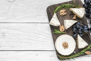 camembert cheese with grapes, walnuts and rosemary on wooden cutting board