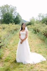 Bride Standing in Farm Field