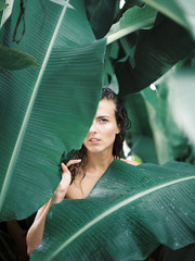 Woman standing in tropic leaves