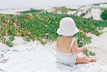 Baby wearing sun hat sitting on beach