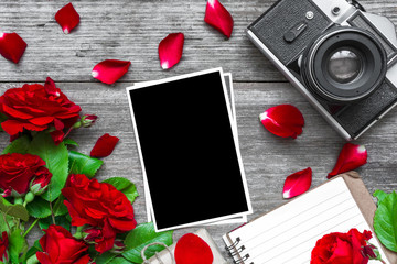 vintage retro camera and blank photo frame with red rose flowers bouquet and lined notebook