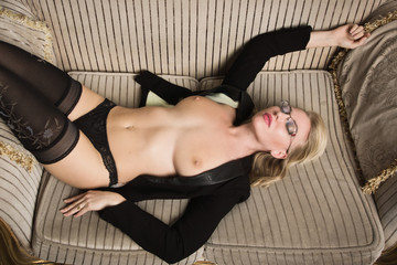 Sexy half-naked woman in glasses and business suit