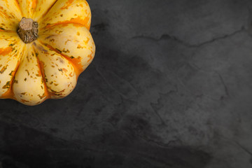 Orange and Yellow Sweet Dumpling Squash on slate background with copy space