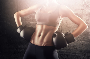 Victorious independent fit woman with boxing gloves posing and showing strength