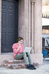 A young man in pink sweater using a laptop and cellphone.