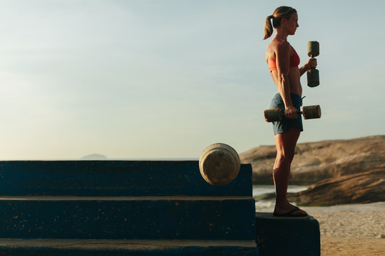 Strong woman exercises on the beach