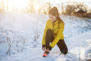 Poster Glisse hiver Portrait view of young satisfied smiling motivated and focused sporty active girl with a ponytail crouching in winter sportswear the snowy nature on the road and tying shoelaces on sneakers.