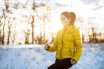 Poster Glisse hiver Portrait view of young satisfied smiling motivated and focused sporty active girl with a ponytail warming in winter sportswear the snowy nature in the morning.