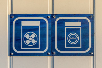 Signs in white and blue, showing illustration of washing machine and dryer