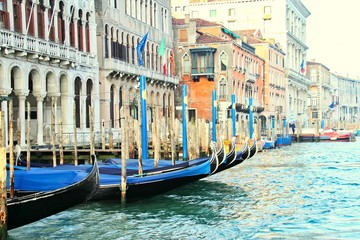 Moored gondolas in a row on the Grand Canal in Venice Italy.