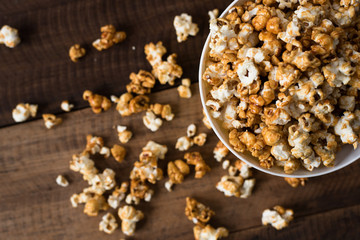 caramel popcorn on wooden table background. caramel flavoured popcorn in bowl