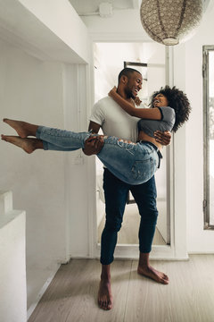 Young black man spinning his girlfriend at home.