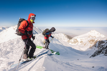 Skiers wearing backpacks and goggles on snow-capped mountain pea