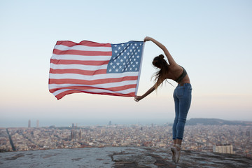 Young woman dancer holding a blowing american flag on a roof at the top of the city