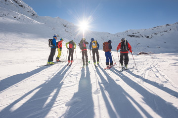 People ski touring in mountains with sun shining brightly