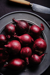 Red onions on a grey metal plate.