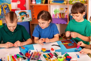 Child dough play in school. Plasticine for children. mold from plasticine in kindergarten. Kids knead modeling clay with hands in preschool. Newcomer in a children's team.