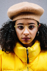 Beautiful mixed ethnicity woman wearing thick yellow puffer jacket and beret.