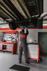 Mechanic working on car in garage/workshop