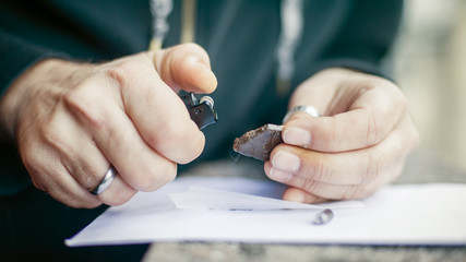 Man preparing hashish joint rolling marijuana cigarette for smoking