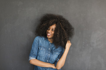 african american woman with big curly hair on the black backgrou