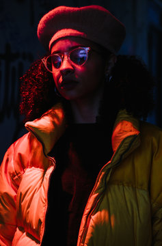 Cool mixed ethnicity woman wearing a puffa jacket standing under an orange spotlight