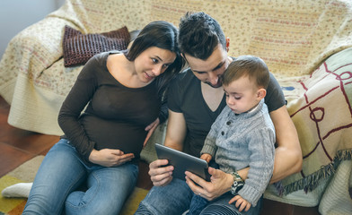 Family with small child and pregnant mother looking at the tablet sitting on the carpet
