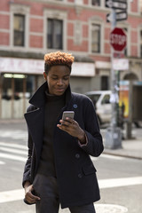 A young black man using a cellphone.