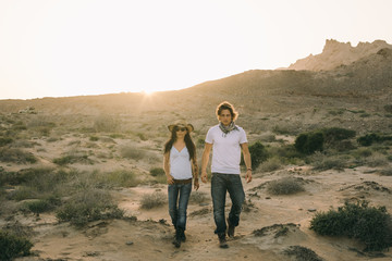 adventurous couple walking in the desert at sunset