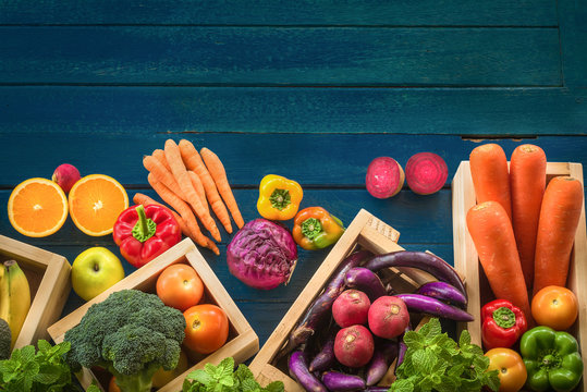 Top view of fresh fruits and vegetables organic on table, Fresh fruits and vegetables in wooden container with copy space on blue plank, Multicolor raw food for healthy lifestyle