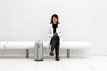 Woman with luggage sitting in bench