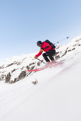 Male skier jumping while riding downhill steep slope