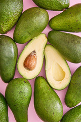 Avocados on pink background.