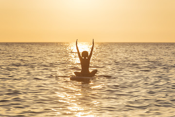 Woman doing Standup paddle at sunset