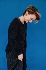 Profile portrait of young female with short hair  wearing black clothes and looking down