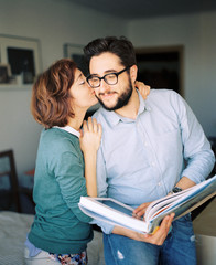 Woman kissing man holding photo album