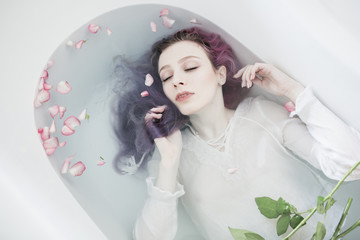 Artistic portrait of a young woman in a baththub
