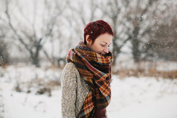 Profile portrait of young female outdoors in winter time wearing sweater and big scarf