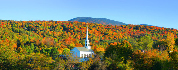 Iconic church in Stowe Vermont middle of fall foliage