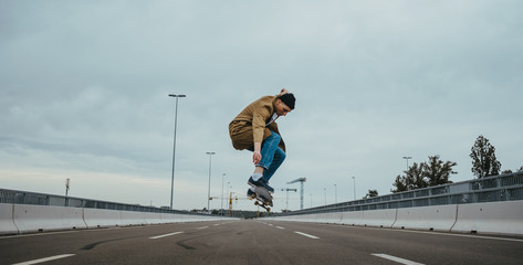 Young authentic urban adolescent/skateboarder on the streets doing tricks.