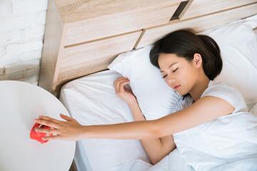 Asian women Pressing alarm clock While she sleeps
