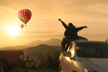 The rear view of the girl relaxing on the car and looking at the mountains with balloons. Asia Tour