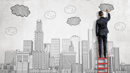 A businessman stands on a ladder and draws a big city with clouds above skyscrapers.
