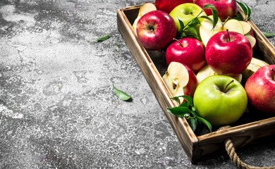 Red and green apples in a wooden tray.