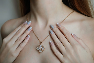 A woman with a french manicure holding a gold chain in the shape of a cross on his neck. Advertising jewelry.