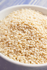 Heap of sesame seeds in white bowl on wooden boards