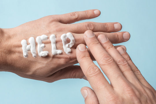 The word Help is written in cream. Painful dry hands of a man in cream or ointment. Blue background
