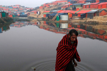 A Rohingya refugee walks next to a pond in the early morning at Balukhali refugee camp near Cox's Bazar