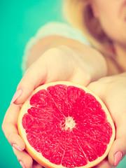 Half of red grapefruit citrus fruit in human hands
